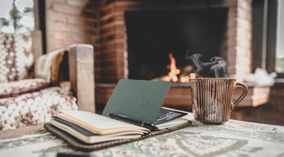Ein Buch liegt auf dem Tisch und im Hintergrund lodert ein Kaminfeuer